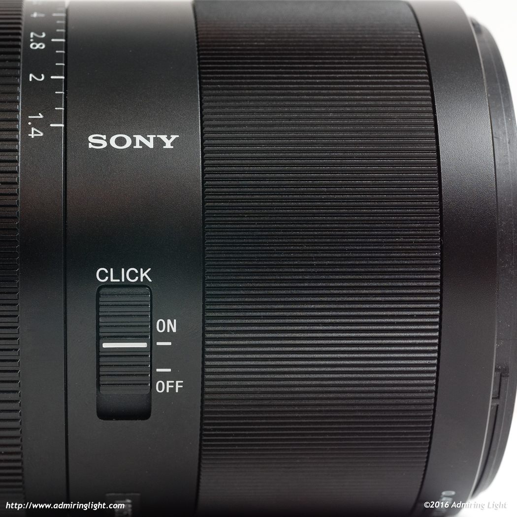 The lens features a switch to toggle the aperture ring detents.